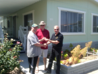 Peter Kling (left) receives his keys to his manufactured home from Richard Simonian (right) of Affordable Community Living. John Yeandle (center) of Santiago Communities adds his congratulations.